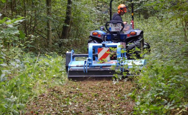 Kleine tractor met klepelmaaier op bosweg