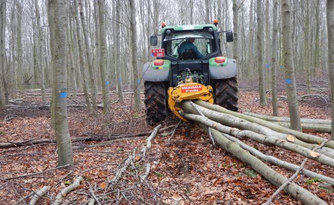 Tractor met uitsleeptang tussen randmarkeringen van vaste ruimingspiste